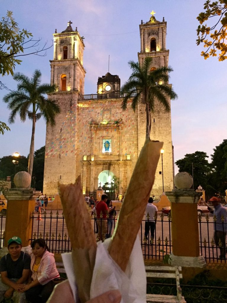 Two crispy pancakes - marquesitas in front of a church in Valladolid, Yucatan. One was with cheese and nutella and the other one with cheese and dulce de leche.