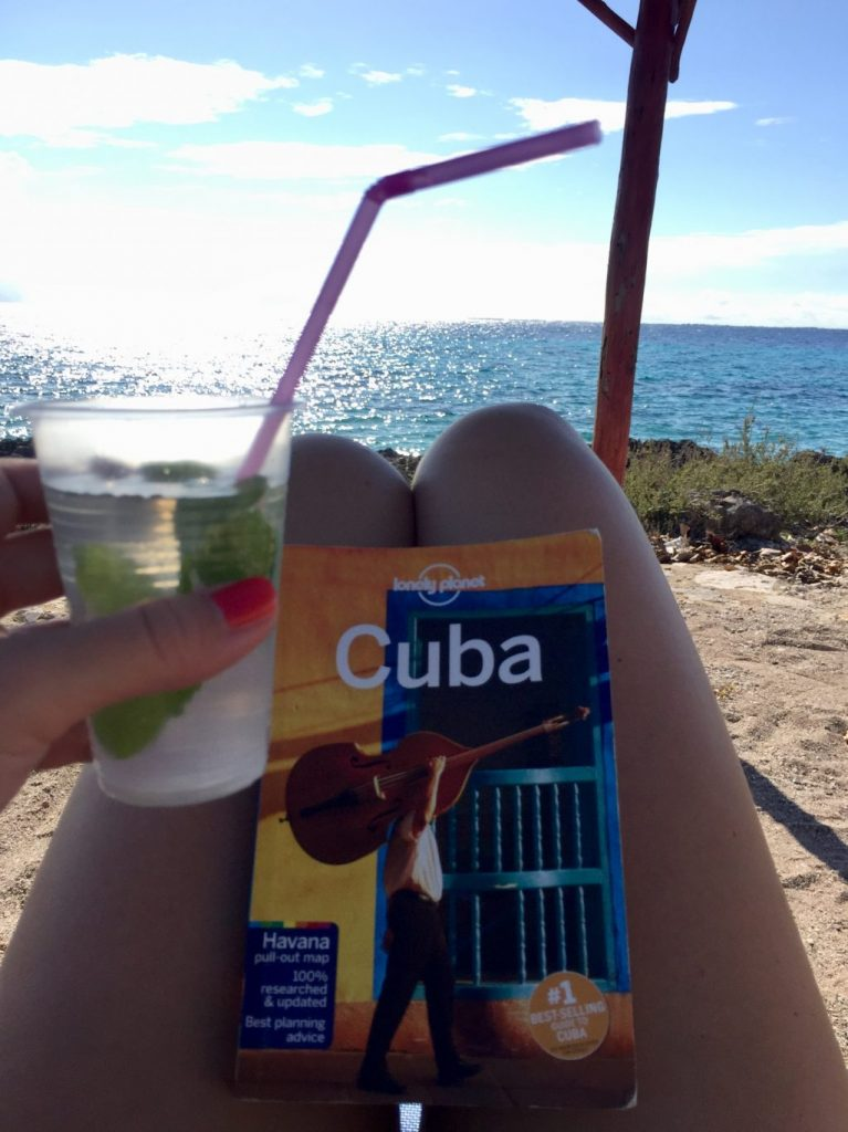 A mojito and a Cuba travel guide at the beach.