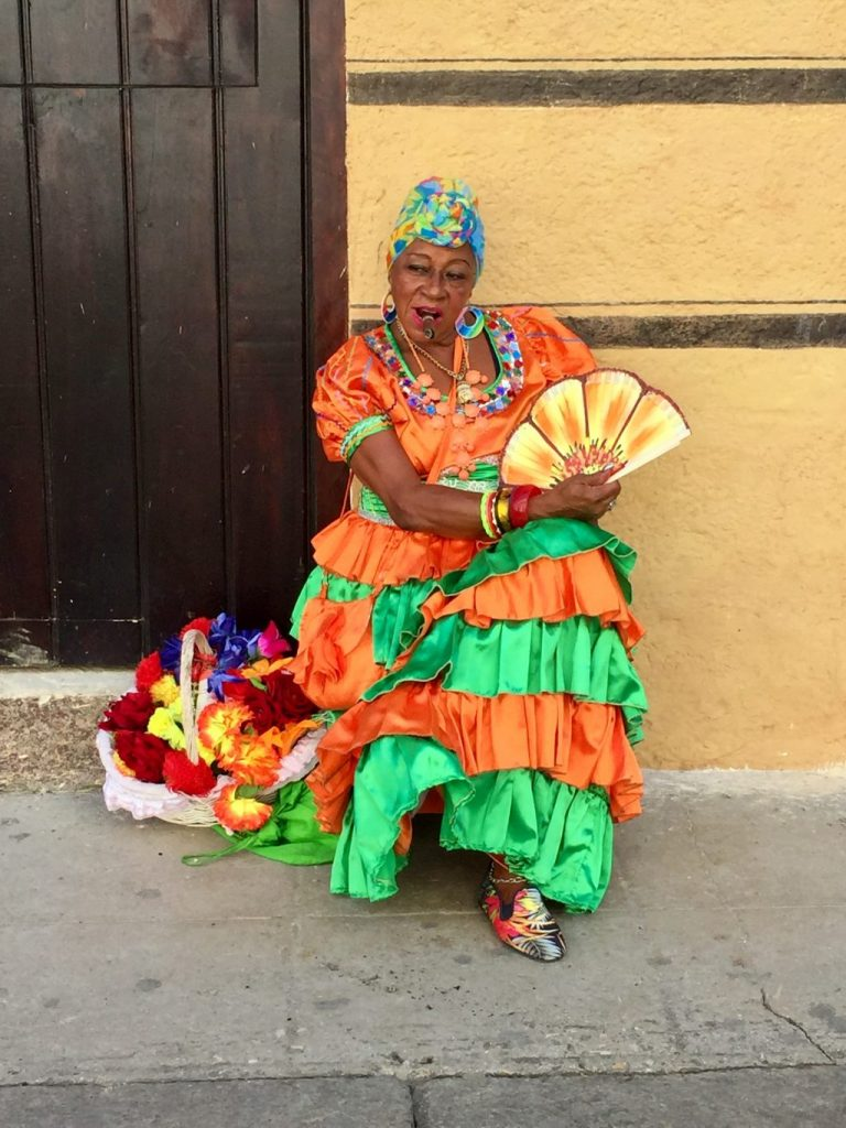 old Cuban lady in a colourful dress smoking a cigar